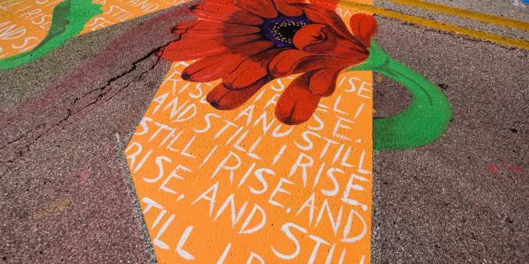 a flower wrapped around a letter painted in the Black Lives Matter mural