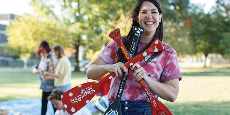A student showcases the painted oars during the annual S'mores N' Oars event.