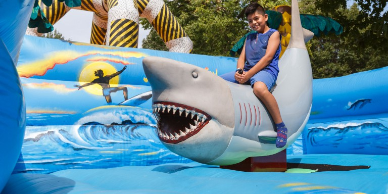 A kid sits on an inflatable shark during one of the festival games.