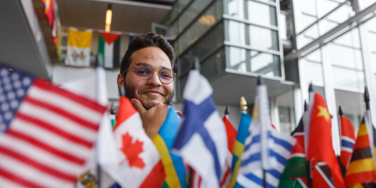 An exhibitor sits behind a collection of mini-flags at the 2020 IUPUI International Festival.