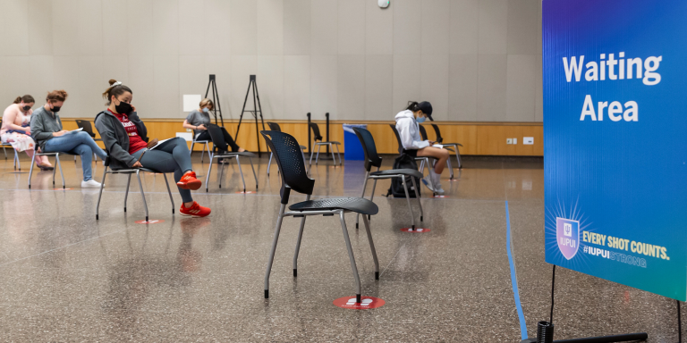 A 'waiting area' sign and seven chairs with people sitting in them after getting vaccinated