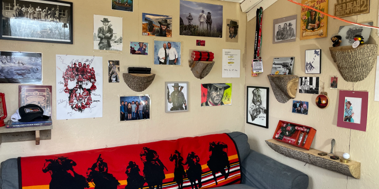 A wall of art and a couch with a blanket