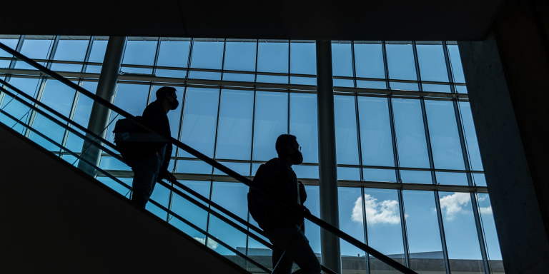 silhouettes of two people on the escalator in the Campus Center