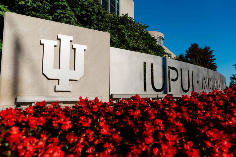 Limestone and metal IUPUI gateway with the IU trident decorated with red flowers.