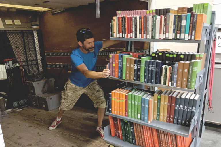 A man attempts to move a 4-tiered stack of hardbound books into a truck.
