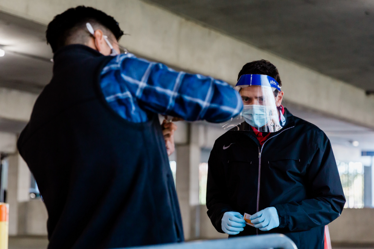 An IU testing site worker watches as a man submits his saliva sample for COVID-19 testing