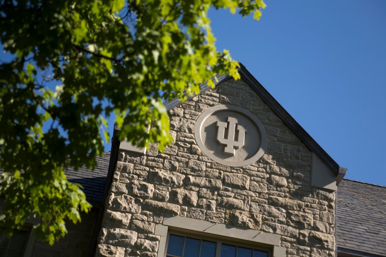 An IU logo adorns the side of the Hutton Honors College on a summer day.