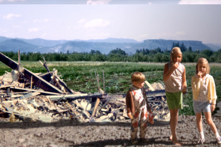 In this billboard image, three children stand near a pile of rubble