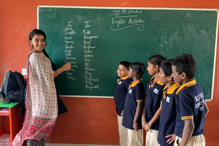 Nidhi Ramanathan stands at a blackboard with students