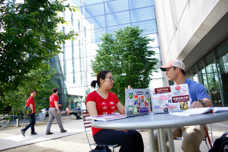 Students sit at a picnic table outside the Global and International Studies Building
