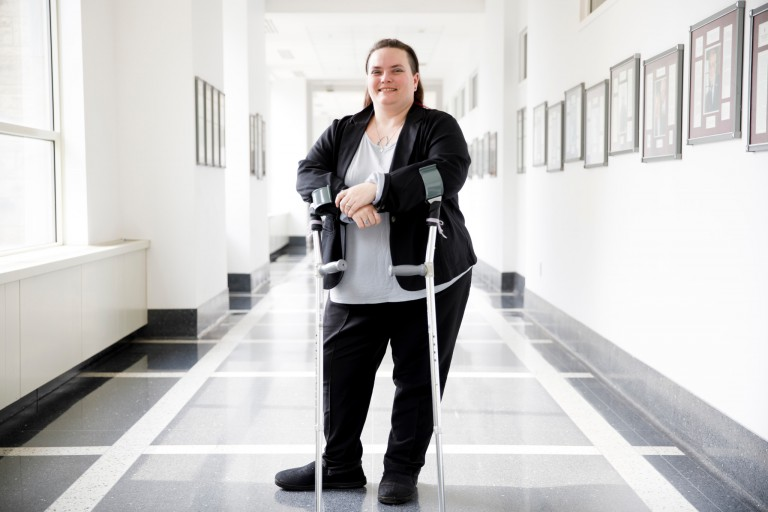 Michelle Abbott standing in the halls in the Kelley School of Business with her walking canes.