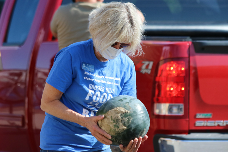 A woman carries a watermelon for a food bank giveaway