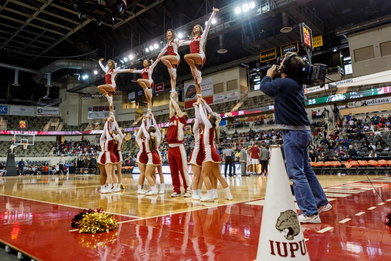 Cheerleaders lift other cheerleaders into the air at a basketball game