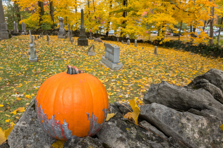a pumpkin rests on a stone wall in a cemetery