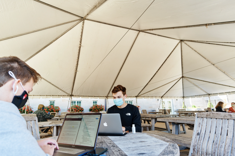 masked students work on laptops while seated under a tent
