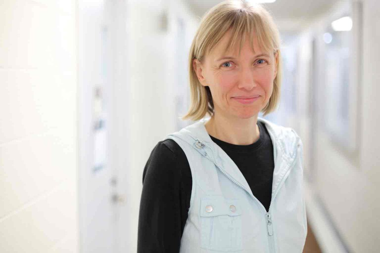 Katy Börner smiles at the camera, she is standing in a long white corridor