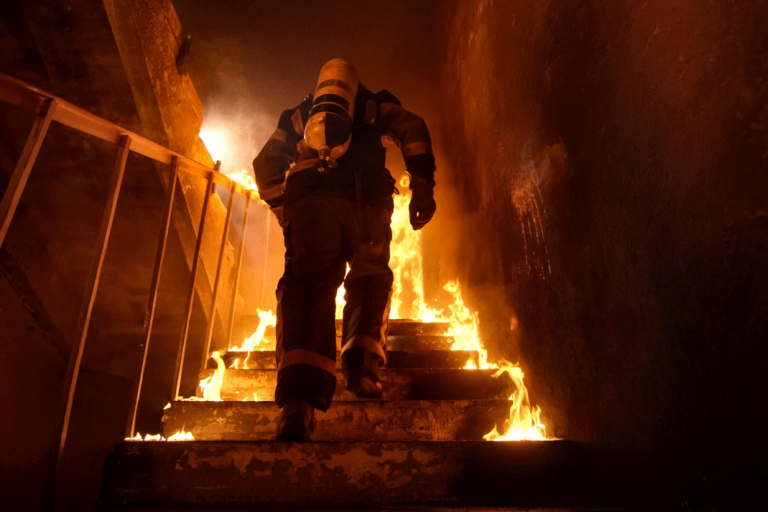 A firefighter running up a burning staircase