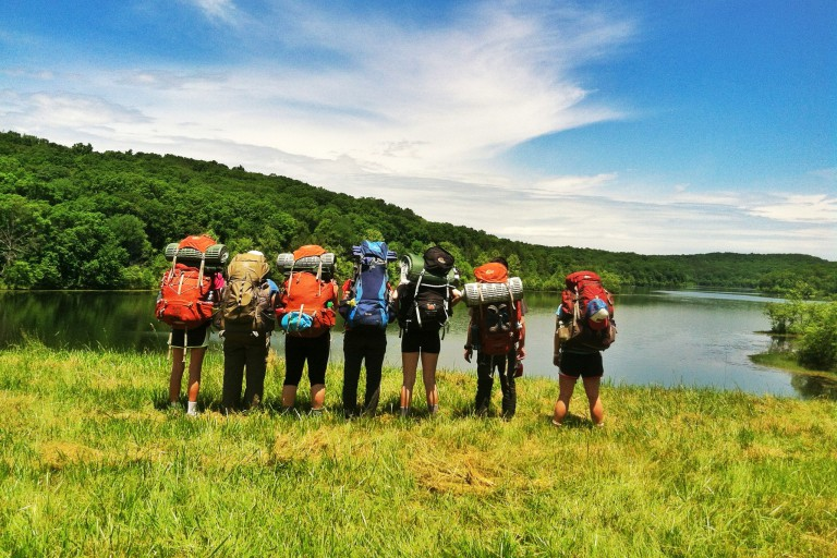 Hikers with backpacks looking at a lake.