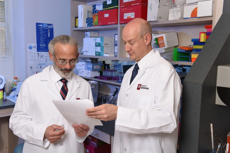 Two researchers wearing white lab coats look at a piece of paper.