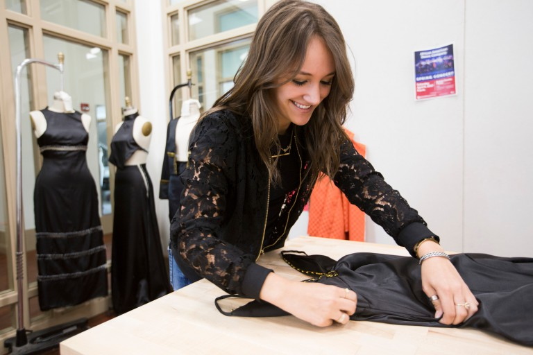 Marley Isaacson working with a dress in a design studio