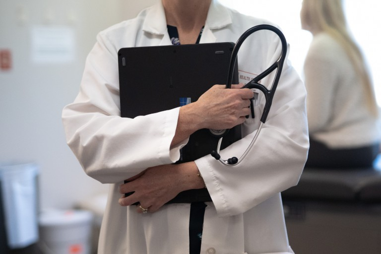 A doctor in a white coat holding a stethoscope