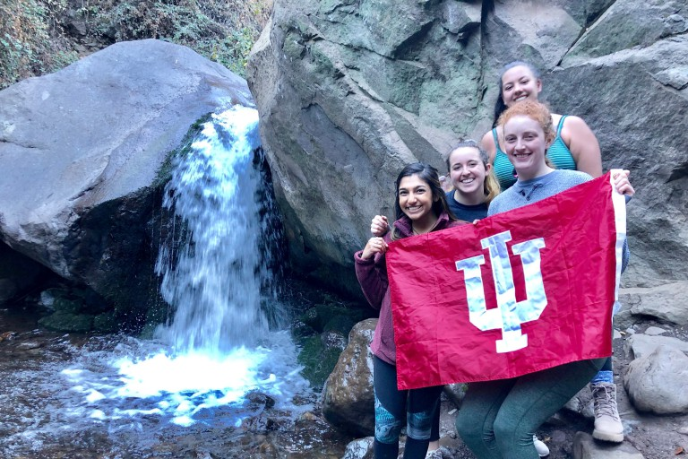 Students raise the IU flag in front of a water fall in Chile