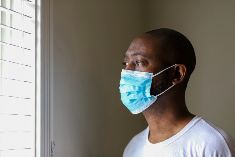 A Black man wearing a face mask looks out a window