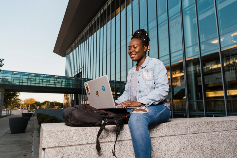 A female student looks at her laptop while sitting outside a building