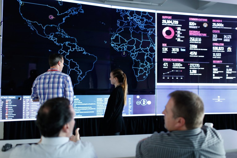 People looking at a world map on a large screen