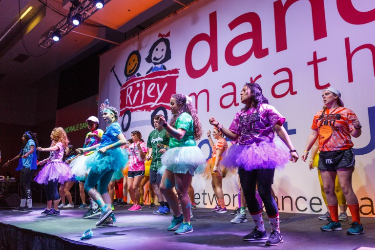 Students in colorful dress dance on stage during Jagathon's Dance Marathon.