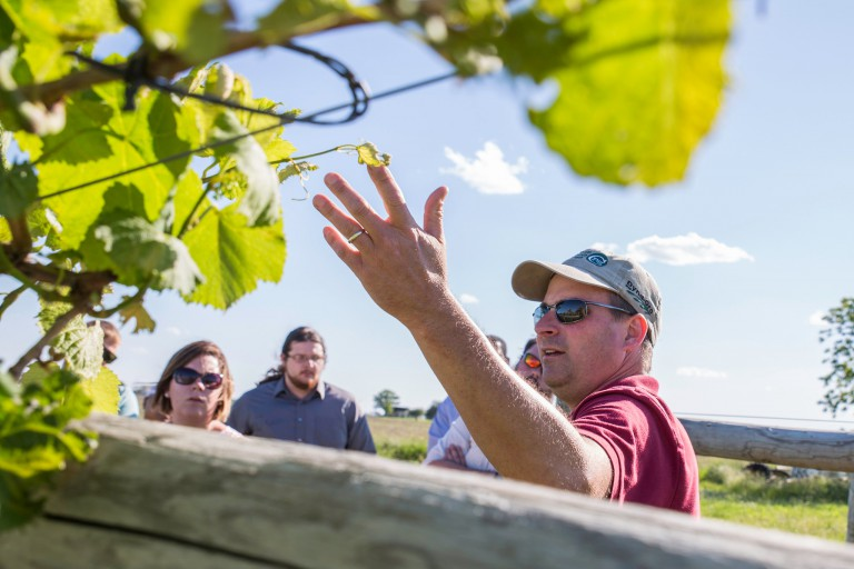 Blackhawk Winery owner John Miller shows IU Kokomo students a grape vine