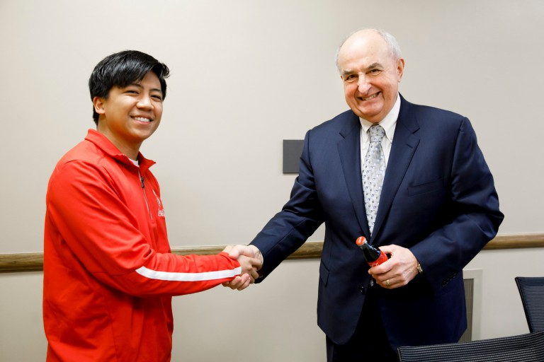 A student shakes hands with IU President McRobbie