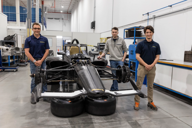 Alex Turner, Parker Neale and Max Grau stand around a race car at the Dallara IndyCar Factory