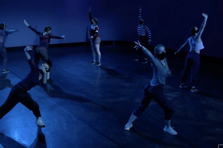 Dancers in two lines pose with their arms extended in dark blue light.