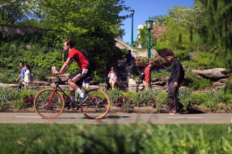 A person rides a bike through campus.