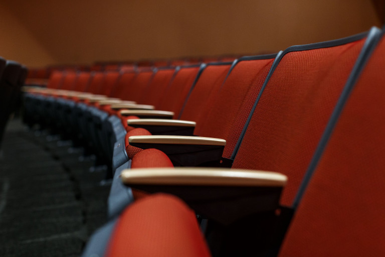 A row of empty red auditorium chairs