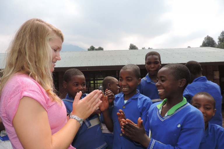 IU student Lillie Hartman plays a hand-clapping game with students from the Kabwende Primary School in Rwanda.