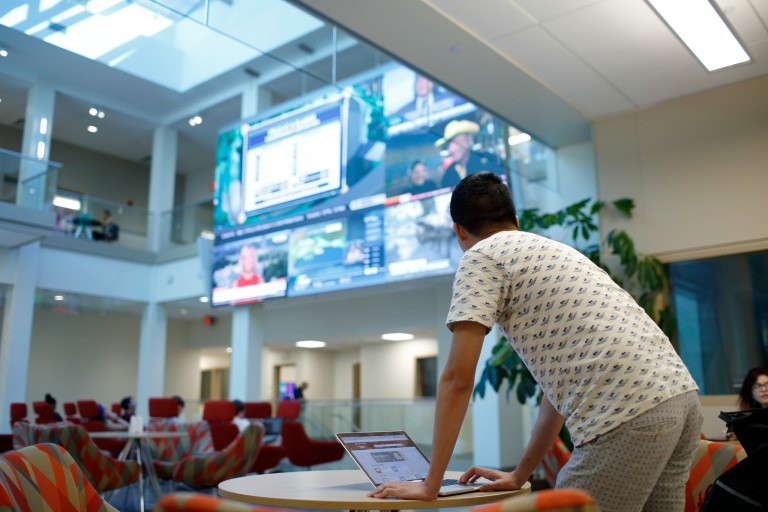 A student in front of a laptop looks up at a huge TV screen with various news channels