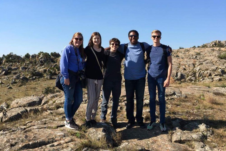 A group of five students pose in a rock outcropping in Africa.
