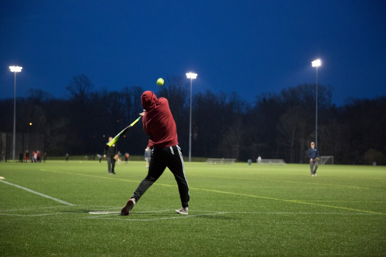 IU employee hits a softball.