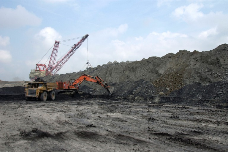 A backhoe and a dragline excavator operate in a surface coal mine.