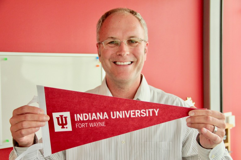 Boyd Bradshaw holds an IU Fort Wayne pennant.