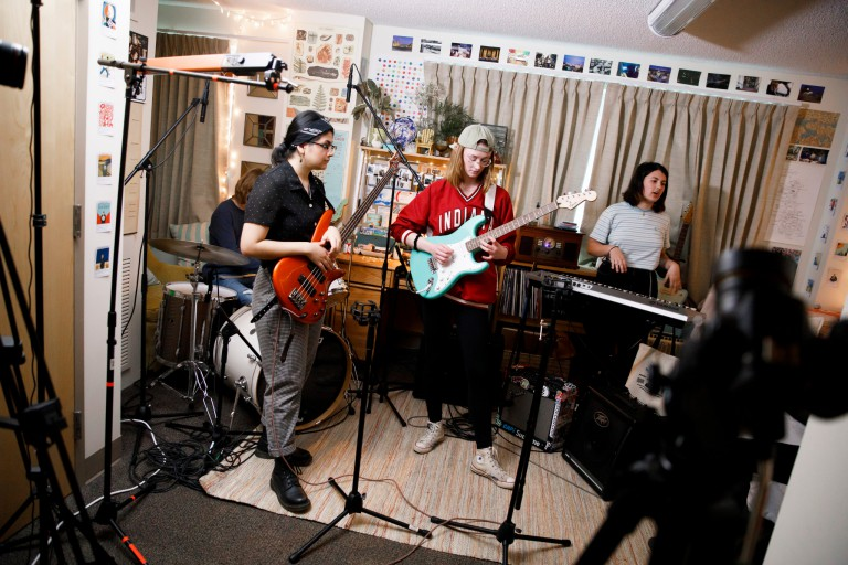 A tiny dorm concert being filmed.