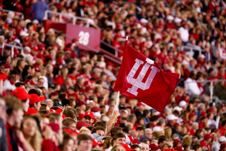 An IU flag waves in the student section during an NCAA college football game.