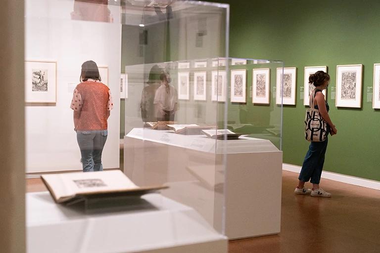 People look at works of art on gallery walls