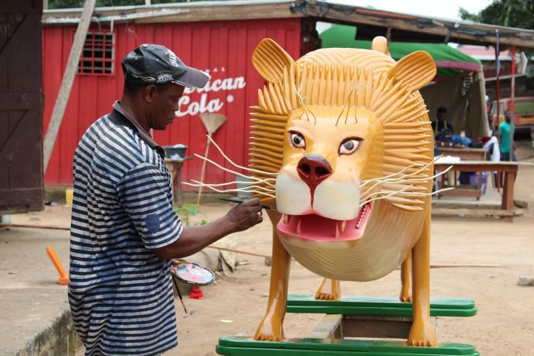 Daniel Anum Jasper hand-paints details on a lion figure.