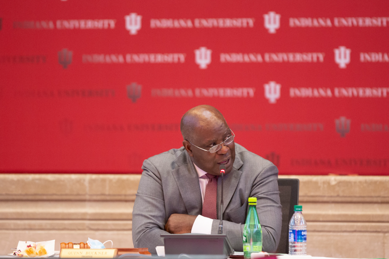 Quinn Buckner sits at a table with a red IU backdrop behind him
