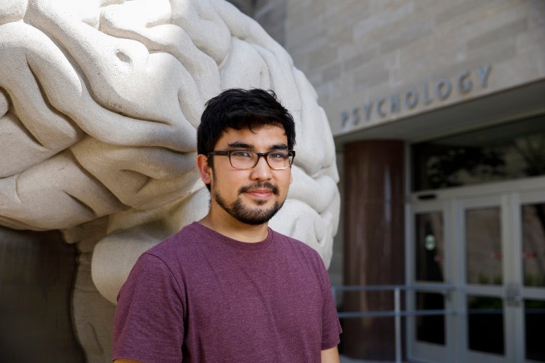 A student stands by the brain sculpture outside the psychology building
