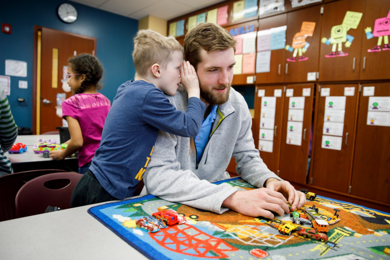 A student whispers into Joey Brunk's ear during indoor recess