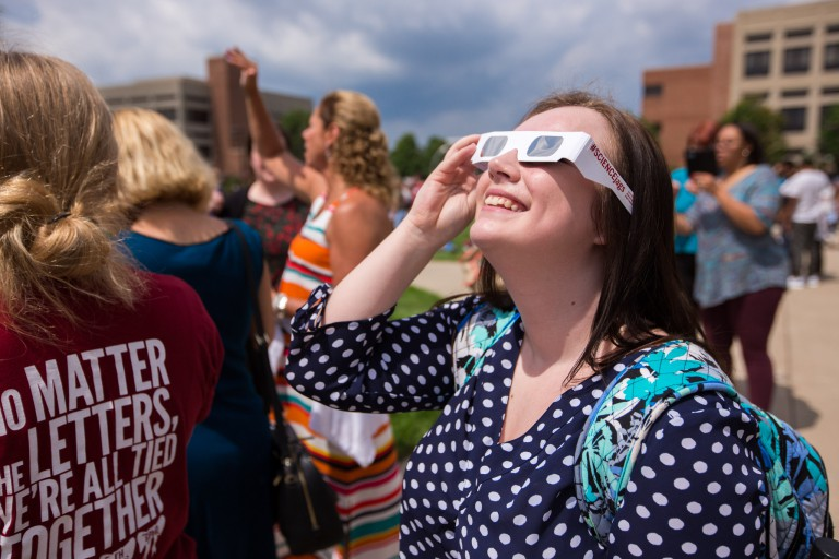 A student looks at the eclipse.